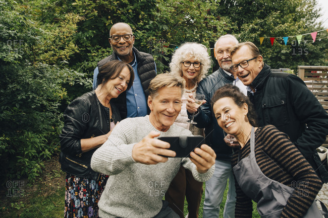 Smiling senior man taking selfie with female and male friends during garden party at back yard