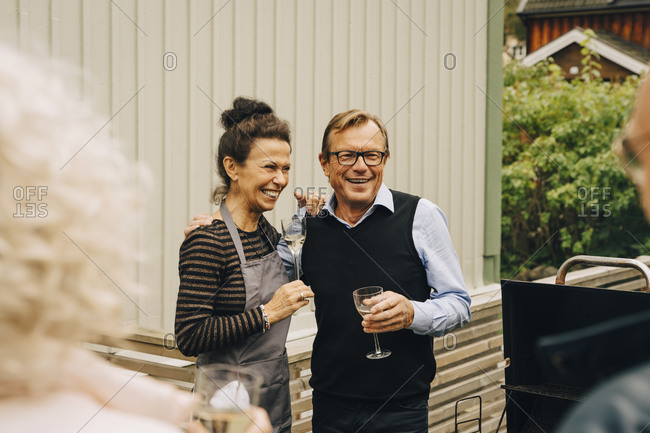 Smiling senior man and woman standing with arm around at back yard during garden party