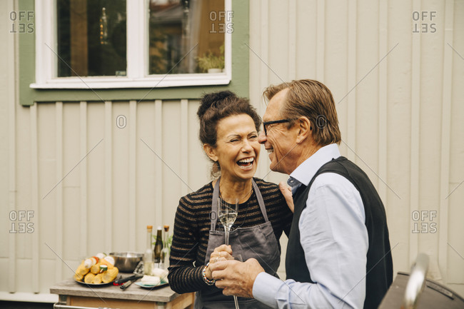 Senior man and woman laughing while holding drink at back yard during party