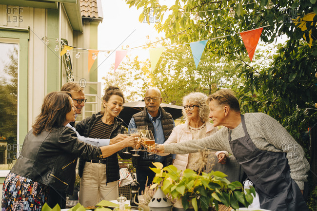 Active senior male and female friends with celebratory toast at back yard during garden dinner party