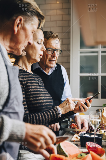 Elderly woman discussing with male friends over smart phone while standing in kitchen at home