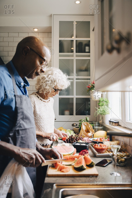 Multi-ethnic senior friends cutting fruits at counter while preparing dinner in kitchen