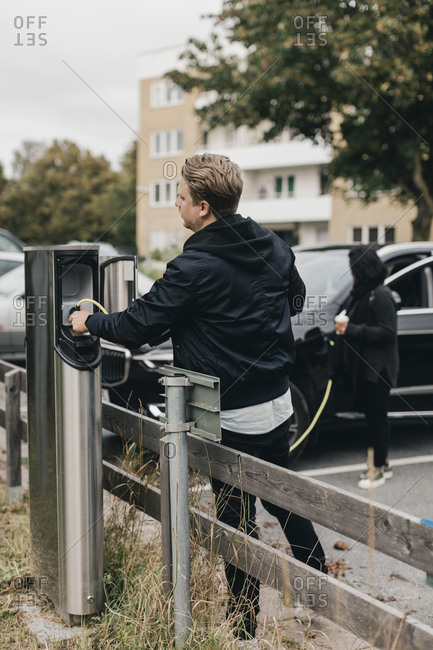 Man connecting cable at electric car charging station