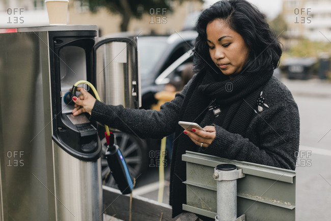 Mid adult woman using smart phone while charging car at station