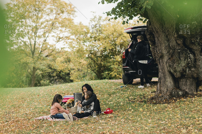 Parents with daughters enjoying picnic during autumn