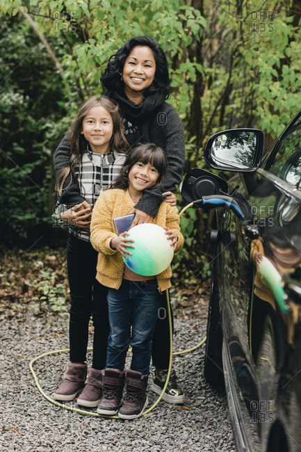 Portrait of smiling woman with daughters by electric car at charging station