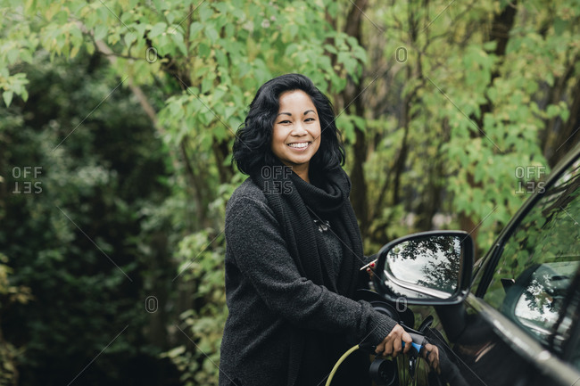 Portrait of smiling mid adult woman charging electric car