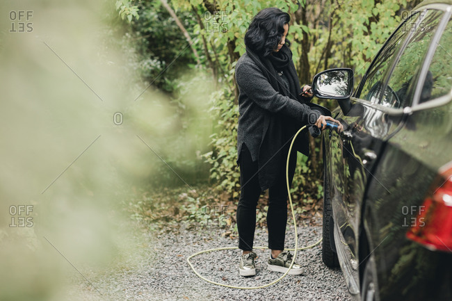 Full length of mid adult woman charging electric car