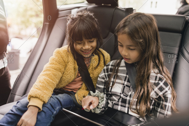 Sisters using digital tablet while sitting in electric car