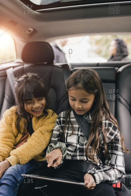 Sisters using digital tablet while sitting in car