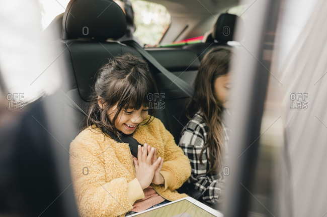 Smiling girl using digital tablet while sitting in car