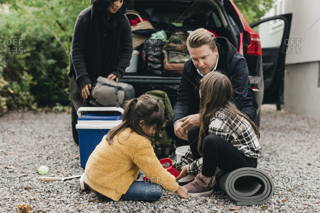 Father talking with daughters while loading luggage in car