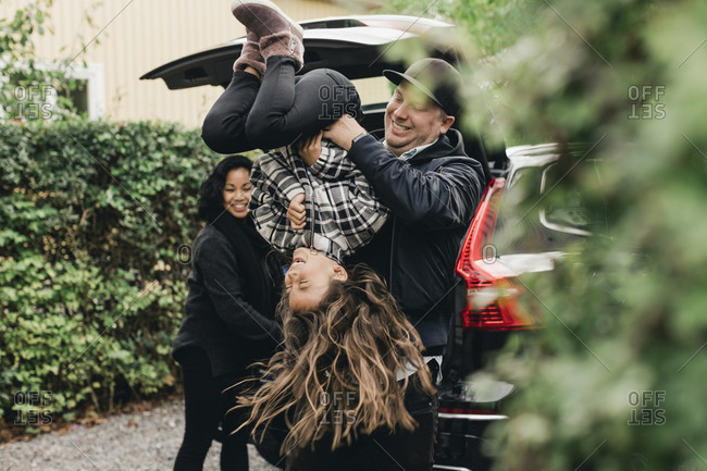 Playful father lifting daughter upside down