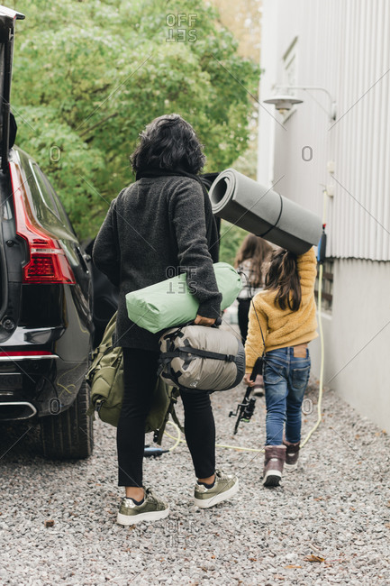 Family unloading luggage from electric car