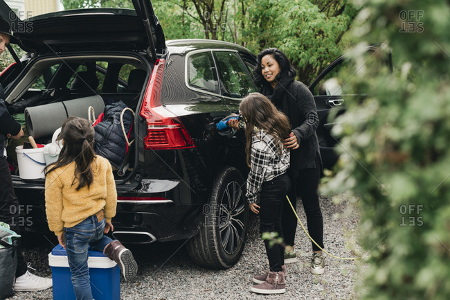 Woman guiding daughter in charging electric car while family loading luggage