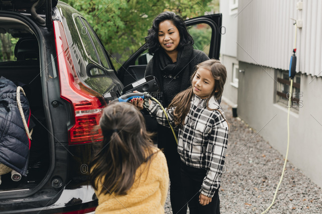 Woman guiding daughter in charging electric car while going for picnic