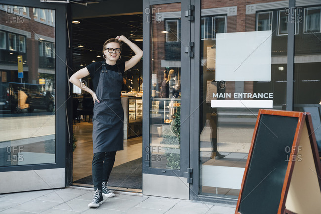 Full length portrait of smiling young owner standing at cafe entrance
