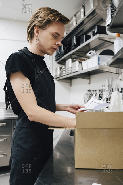 Side view of young androgynous barista holding list by cardboard box in cafe kitchen