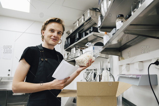 Portrait of smiling transgender owner with list and package in coffee shop kitchen