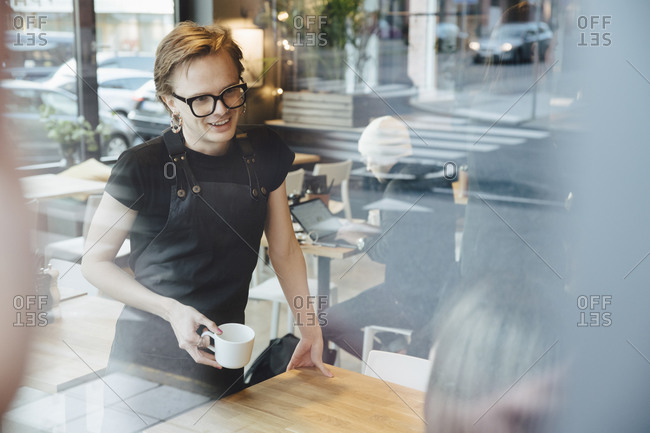 Smiling androgynous barista talking with customer in coffee shop