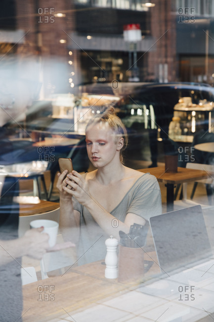 Young androgynous customer using smart phone while sitting in cafe seen from window