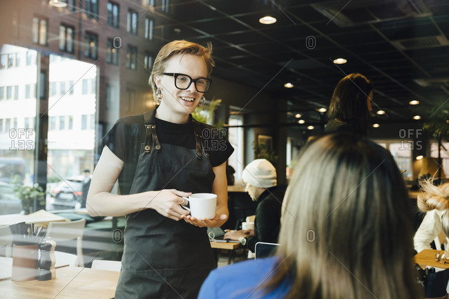 Smiling young transgender barista looking while talking with female customer in cafeteria