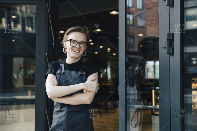 Portrait of smiling androgynous owner standing with arms crossed at coffee shop entrance