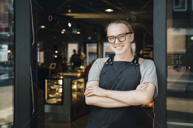 Portrait of smiling androgynous owner standing with arms crossed at cafe doorway