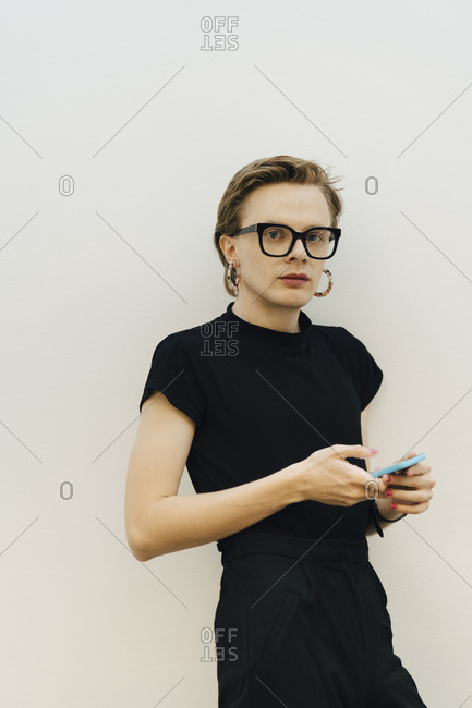 Confident androgynous entrepreneur standing with smart phone against while wall in board room