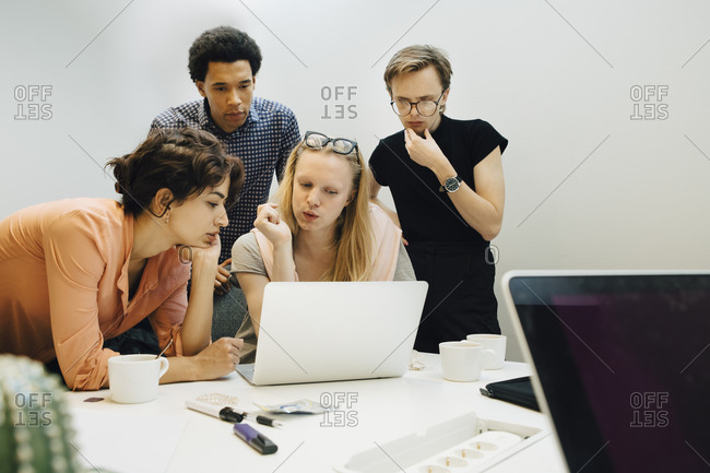 Multi-ethnic colleagues planning strategy while looking at laptop in illuminated office board room