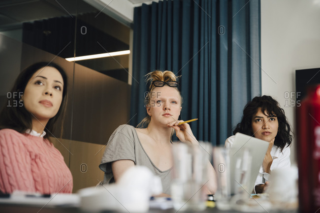 Transgender professional sitting amidst businesswomen in board room during meeting