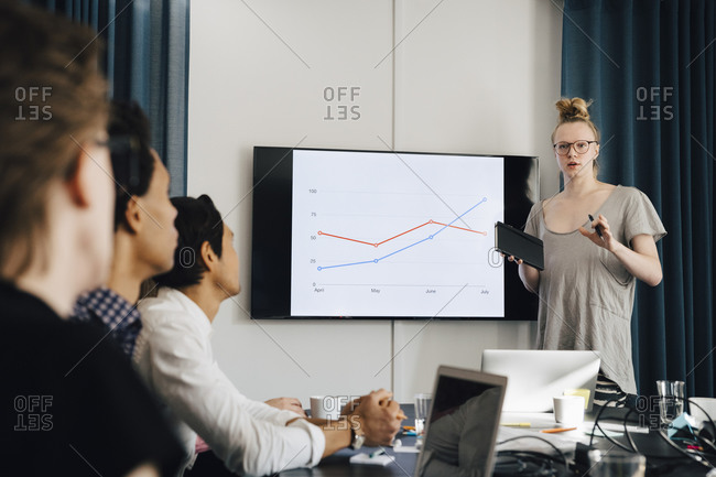 Confident genderblend businessman explaining strategy over graph to colleagues in board room during meeting