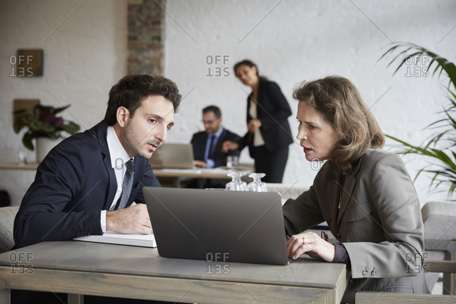 Senior female lawyer discussing over laptop with young businessman during meeting at office