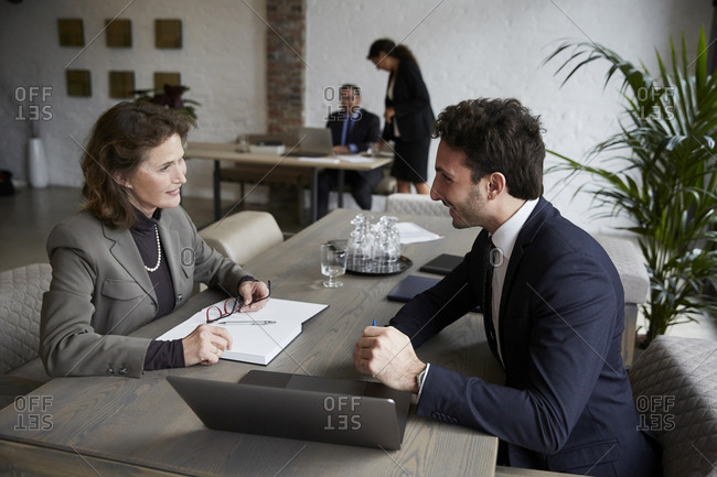 Confident senior female lawyer smiling while discussing over laptop with young businessman during meeting at office