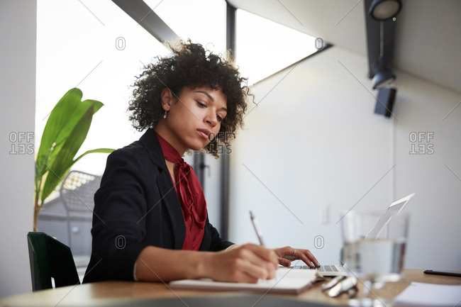 Confident young female financial advisor writing on diary while sitting with laptop at desk in office