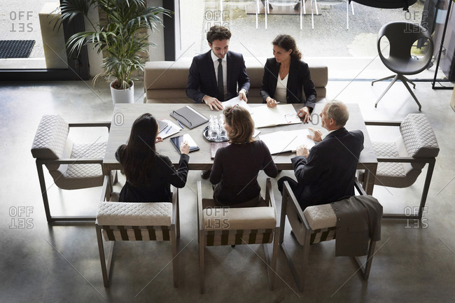 High angle view of financial advisors and customers discussing during meeting at law firm