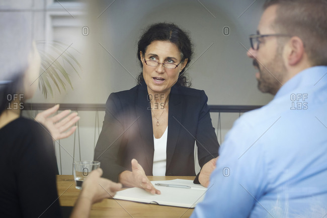 Confident mature female lawyer discussing with businessman and businesswoman during meeting at office