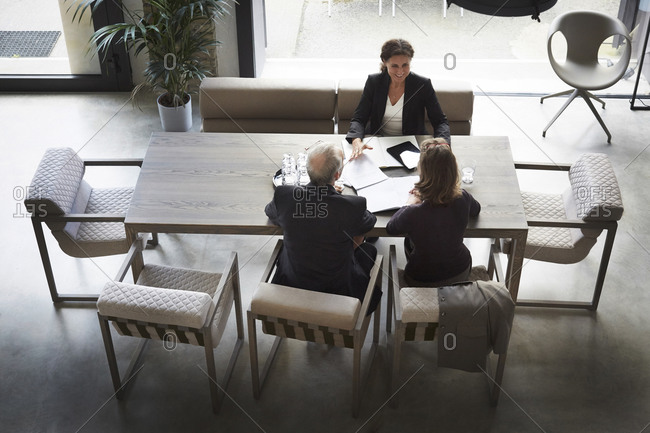 High angle view of female lawyer and customers sitting at desk in office