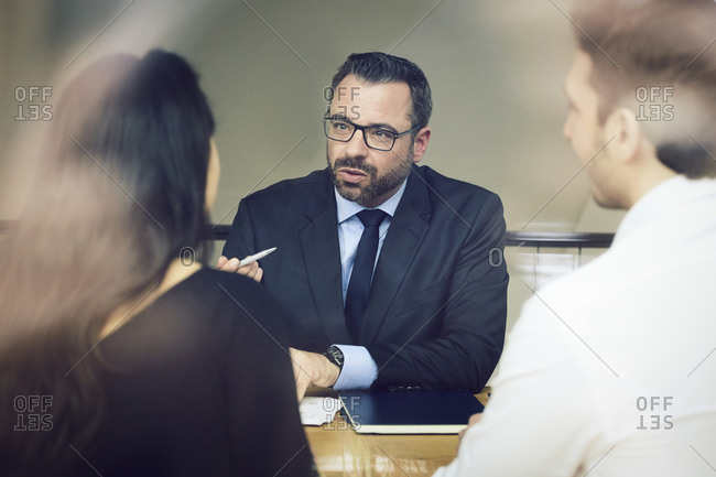 Confident mature male lawyer discussing with customers at office