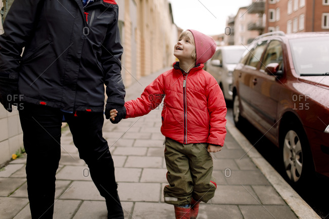 Smiling grandson in warm clothing holding hands of grandmother while walking on footpath