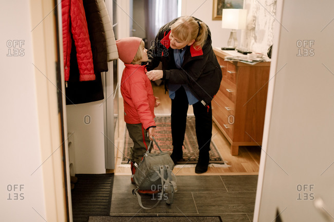 Senior woman wearing warm clothes to grandson at home