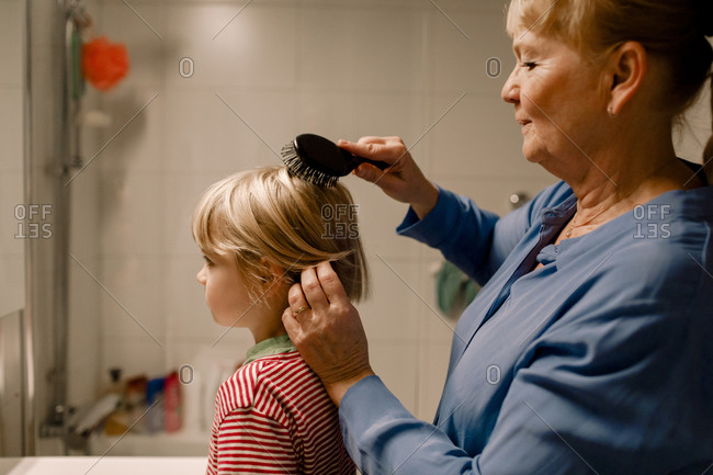 Side view senior woman combing hair of grandson in bathroom at home