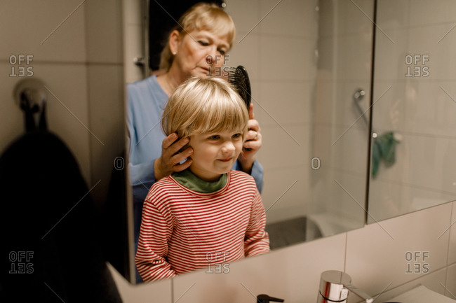 Senior woman combing hair of grandson in bathroom at home