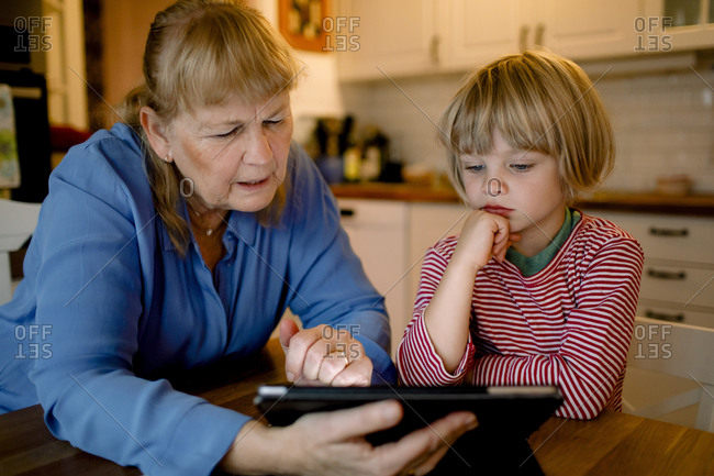 Boy looking at grandmother using digital tablet