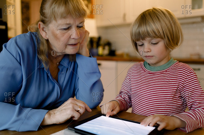 Senior woman looking at grandson using digital tablet