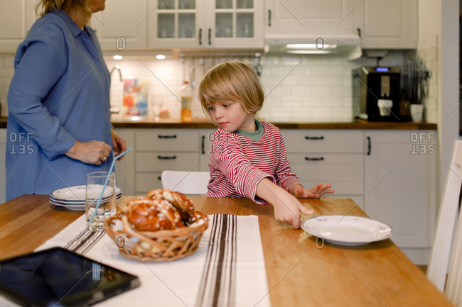 Boy with grandmother in kitchen at home