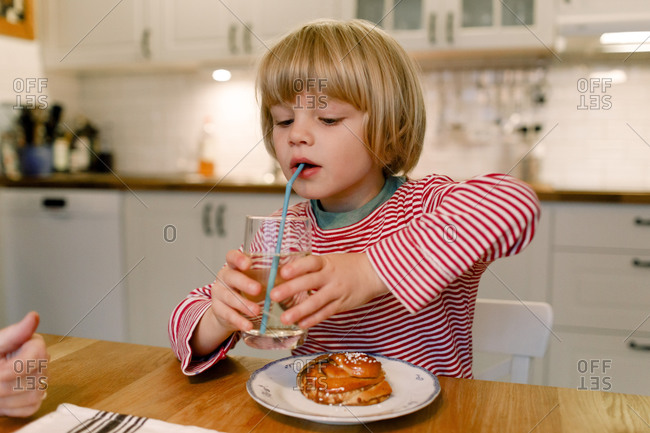 Boy having drink at dining table