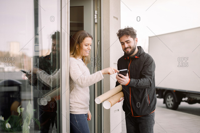 Female customer signing on smart phone while receiving package from delivery man