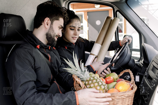 Young delivery man and woman with fruits and packages in truck