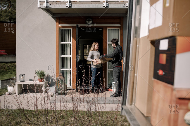 Delivery man delivering package to customer at entrance of house